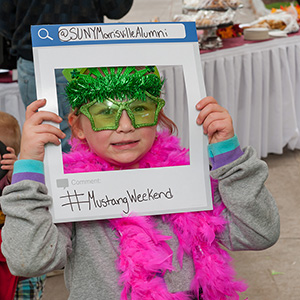Decorated child holds up a #MustangWeekend photo frame